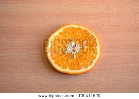 One slice of mandarine orange on a wooden background