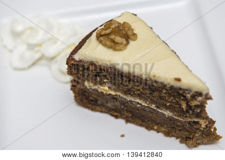Slice of walnut cake served with whipped cream