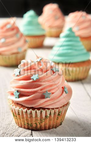 Cupcakes with turquoise and pink cream decarated with star-shaped culinary sprinkling
