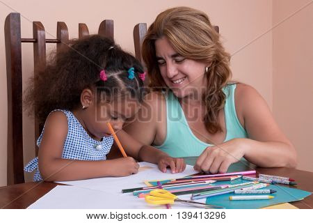 Small multiracial girl and her mother drawing with color pencils at home