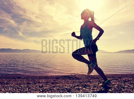 healthy young fitness woman runner running on sunrise seaside
