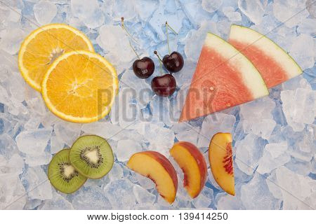 Various fruit on ice. An assortment of fruit slices and wedges on ice.