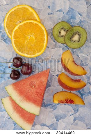 Assortment of fruit slices and wedges on ice.