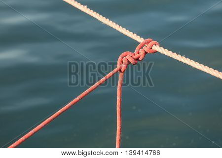 Closeup of knot on rope line over sea ocean water.
