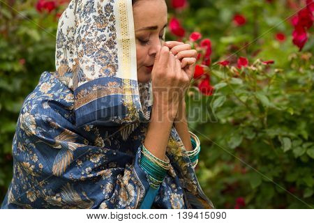 Woman in beautiful shawl and necklace prays among rose bushes in park