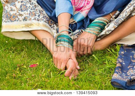 Barefoot feet of indian woman in bright sari sitting on grass in garden