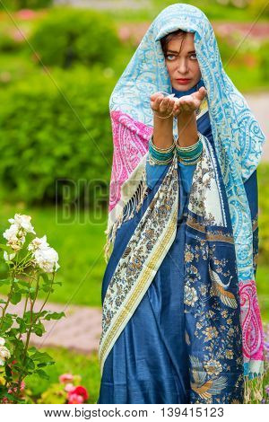 Middle age woman in blue sari and Indian adornment holds petals in summer park