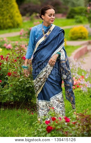 Happy woman in indian bright sari walking on grass in garden at summer
