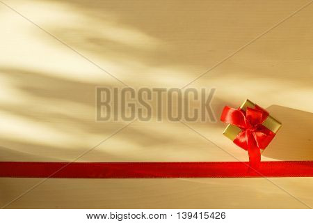Holidays present concept. Small golden box with gift tied decorative bow and red ribbon frame