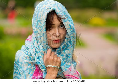 Sad indian woman stands and looks at camera in bright sari in garden