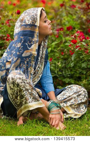 Middle age woman in blue sari and Indian adornment sits on lawn near roses