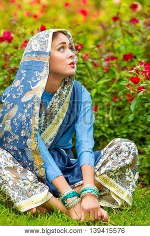 Middle age woman in blue sari and Indian adornment sits on lawn in garden