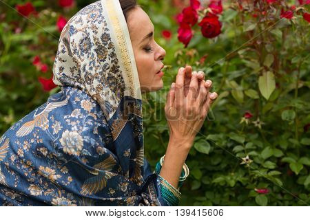 Woman in sari and bracelets prays among red rose bushes in garden