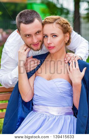 Woman in dress and jacket sits on bench and man hugs her in summer park