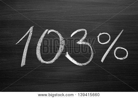 103 percent header written with a chalk on the blackboard