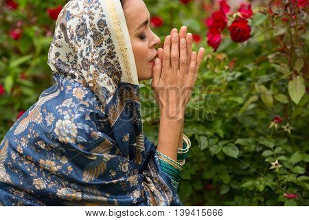 Woman in sari and bracelets prays among red rose bushes in park