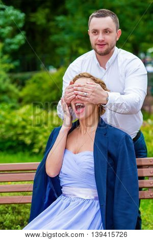 Woman in dress and jacket sits on bench and man closes her eyes in green summer park, focus on girl