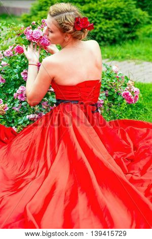 Woman in long red dress poses near flowers in summer garden, back view