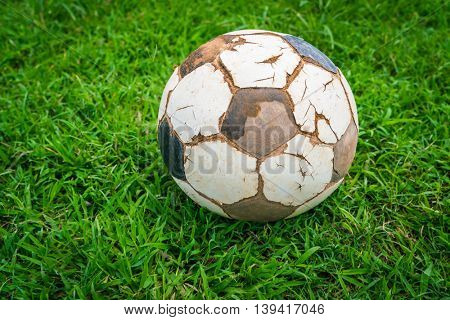 Old soccer ball on fresh spring green grass