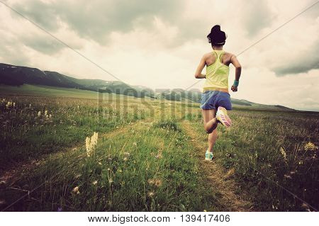 healthy young woman trail runner running on beautiful prairie trail