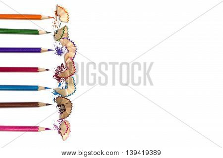 Color pencils with color pencil shavings on white background