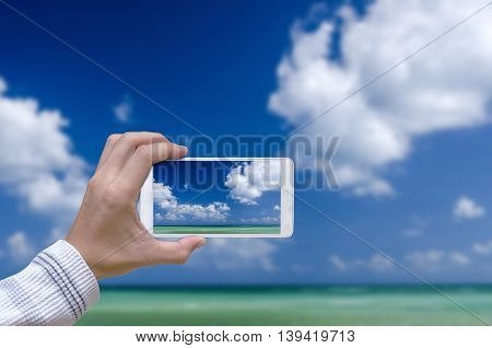 man hand with smartphone taking pictures the blue sky and sea.