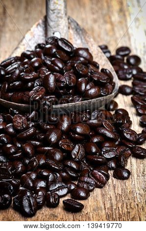 coffee beans in wooden spoon on wooden background.