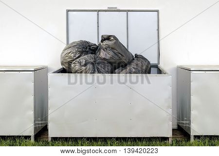 black garbage bags in metal box out side the building.
