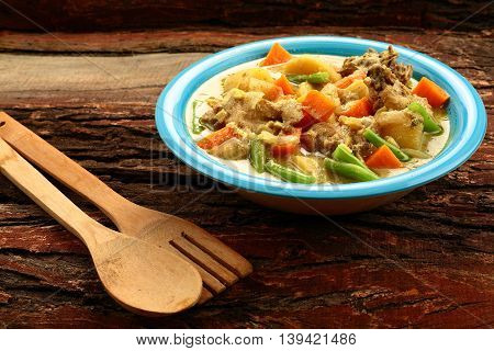 Mild and tasty mutton curry on wooden background,