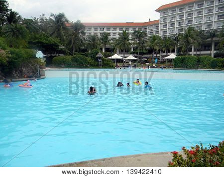 LAPU LAPU, CEBU / PHILIPPINES - JULY 28, 2011: People enjoy swimming in the swimming pool of Shangri-La's Mactan Resort and Spa.
