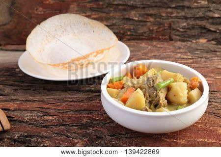 Mutton and vegetable stew served with Appam.