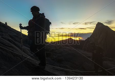 Mount Kinabalu,Ranau,Sabah Borneo-March 12,2016:Climber passing trail to the summit Mount of Kinabalu in the early morning.At the granite plateau summit awaits a spectacular view of verdant mountain ranges.