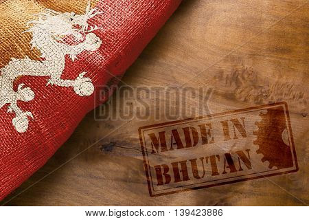 Hot stamping Made in Bhutan on a wooden background.