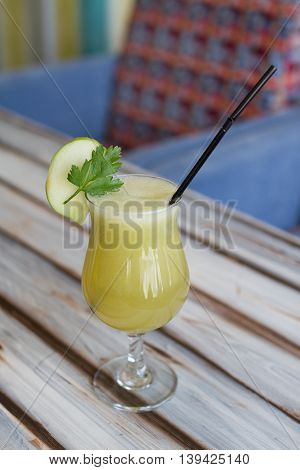 Glass of freshly squeezed pineapple juice on a wooden table