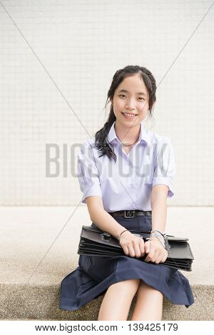 Cute Asian Thai high schoolgirl student in school uniform sitting on the stair and showing smiling happy facial expression in white building background