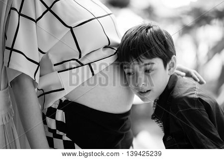 Little boy listen mother belly pregnancy wating for new baby