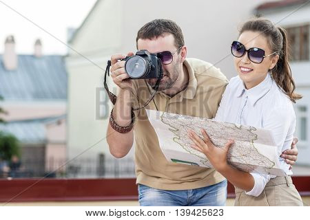 Young Tourist Couple in Town Outdoors Taking PIctures Together. Happy Couple Vacation. Horizontal Image