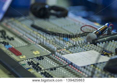 Professional Mixing Console Closeup During Work Time. Microphone and Headphones on Surface. Horizontal Image