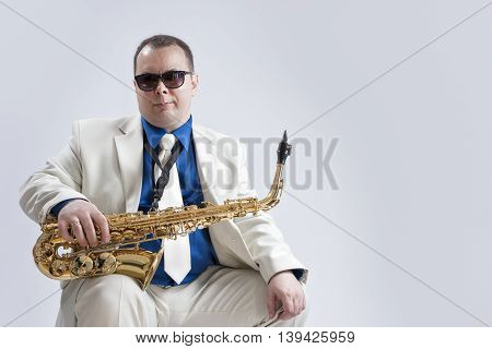 Portrait of Caucasian Saxophone Player Posing with Instrument In Sunglasses Against White Background. Horizontal Shot