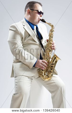 Portrait of Hadnsome Male Saxophone Player Playing in Studio Environment. Wearing Stylich Suit and Sunglasses. Vertical Image Orientation