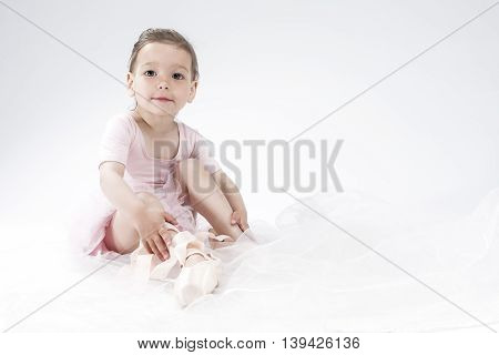 Little Girl Posing as Ballerina in Toes. Against White Background. Horizontal Image Composition