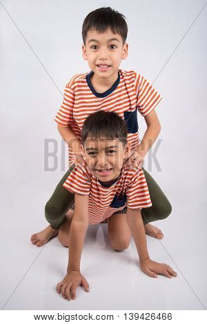 Little siblings boy brother smiling laying down together with happy face on white background