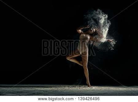 Amazing photo of graceful woman dancing with dust in studio