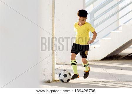 Boy Play Football Under The Empty Building