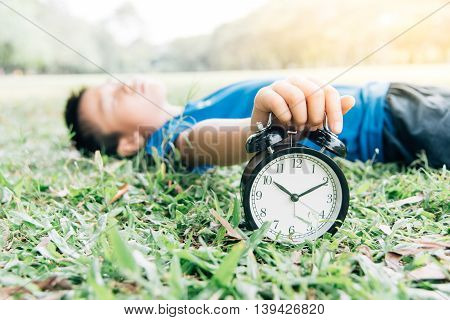 Black Alarm Clock And Sleeping Boy In The Park
