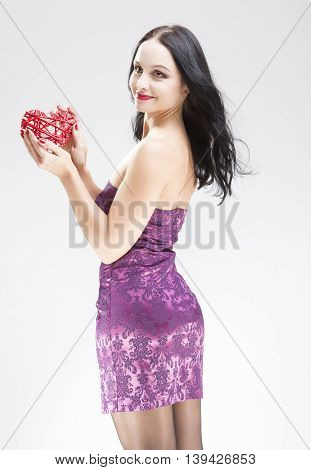 Portrait of Smiling Sensual Brunette Woman Holding Symbolic Red Weaved Heart In Front. Over White. Vertical Shot