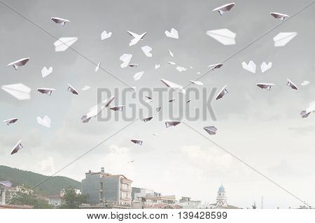 Paper planes flying in air . Mixed media