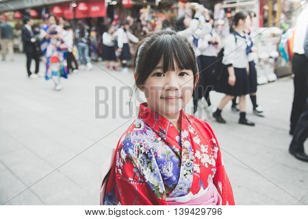 Beautiful Asian girl wearing red kimono walking in the cityAsakusa Tokyo Japan.