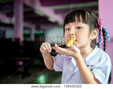 Asian Girl Child Eating A Crispy Wonton