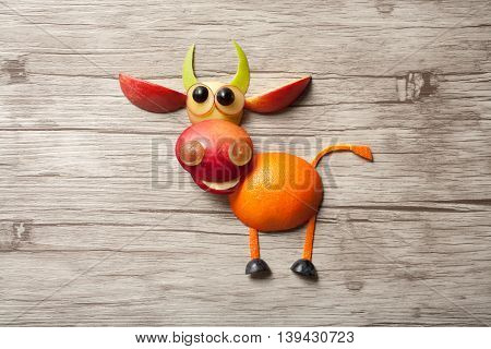 Bull made of apple on wooden background